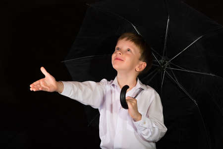 boy barefoot: Portrait of a boy on a black background with the white shirt. Blue eyes blond. With umbrella in hand while standing.