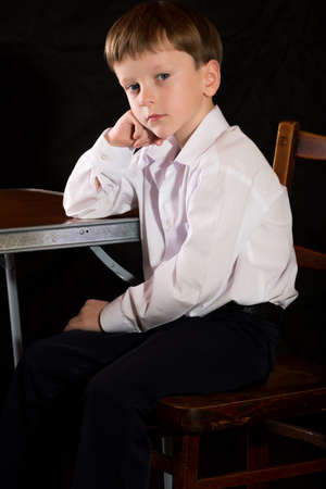 full face: Portrait of a boy on a black background with the white shirt. Blue eyes blond. Sitting at the table.