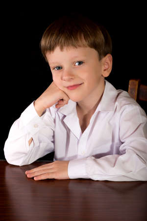 boy barefoot: Portrait of a boy on a black background with the white shirt. Blue eyes blond. Sitting at the table.