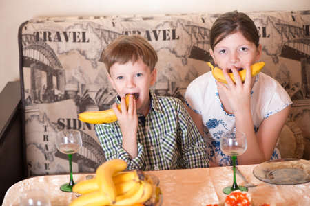 fullface: Portrait a fullface of the smil girl and the boy s at a table with bananas