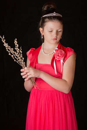 full willow: Portrait of the girl in a red dress on a black background with a bunch of willow in hand.