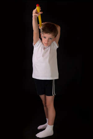 boy shorts: Boy student athlete performs exercises with gymnastic stick in the gym. Demonstrates learning postures sport for gymnastics. Stock Photo