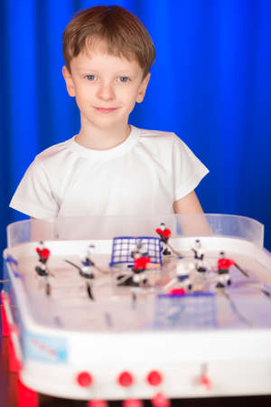 scored: Boy playing table hockey. A child holds a hockey game at the table. Schoolboy hockey referee .