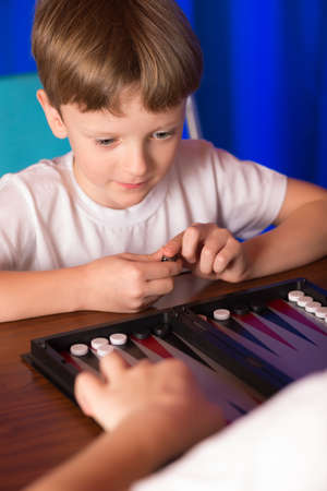 rival rivals rivalry season: boy playing ancient Eastern game called Backgammon