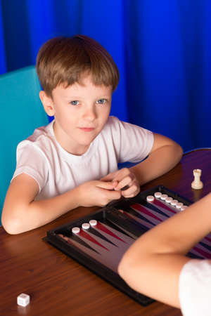 doubling: boy playing ancient Eastern game called Backgammon