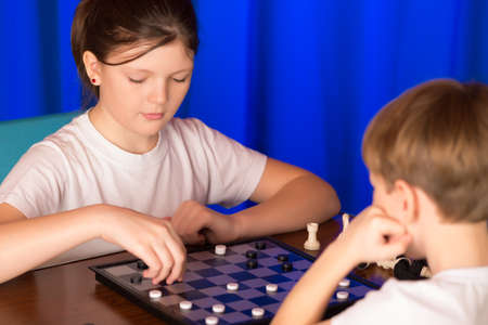 doubling: Children play a board game called checkers. Passes blitz. Stock Photo