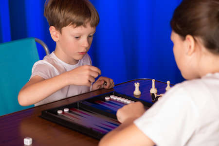 rival rivals rivalry season: boy and girl playing in the ancient oriental game called Backgammon