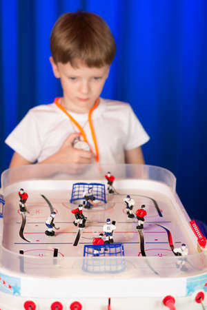 scored: Boy playing table hockey. A child holds a hockey game at the table. Schoolboy hockey referee . Sporting future generation.