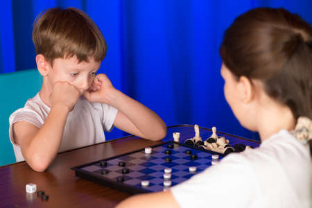 shootout: Children play a board game called checkers. Passes blitz. Stock Photo