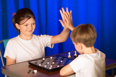 doubling: Children play a board game called checkers. Passes blitz. They greet one another with a blow palms.