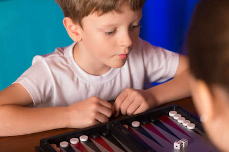 backgammon: boy playing ancient Eastern game called Backgammon