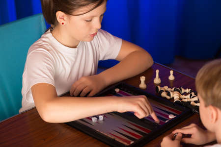 doubling: boy and girl playing in the ancient oriental game called Backgammon