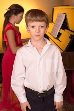 pianista: El muchacho canta con el acompañamiento de un piano. Cantante y pianista. Foto de archivo