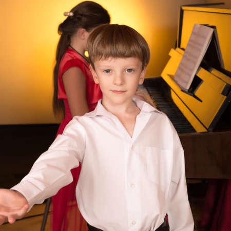 pianista: El muchacho canta con el acompa�amiento de un piano. Cantante y pianista. Foto de archivo