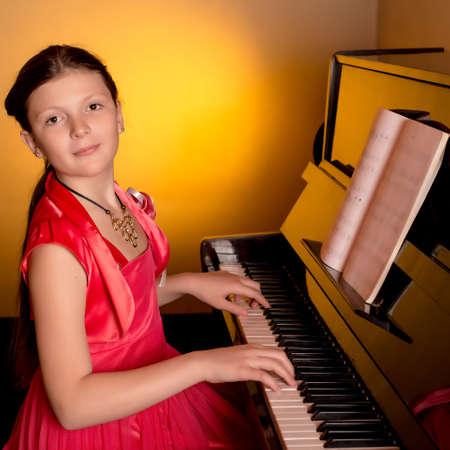 tocando piano: Chica joven que juega el piano. Pianista. Foto de archivo