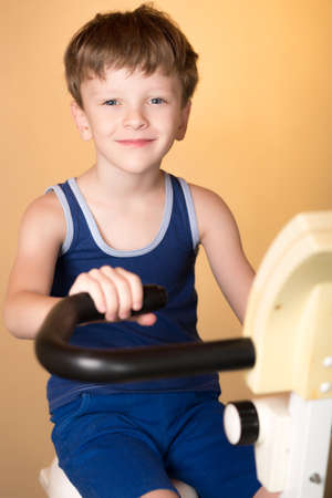stationary bike: The child is trained on a stationary bike . Leads a healthy lifestyle. The boy develops muscles . Tired and sweaty . Sport generation. Stock Photo