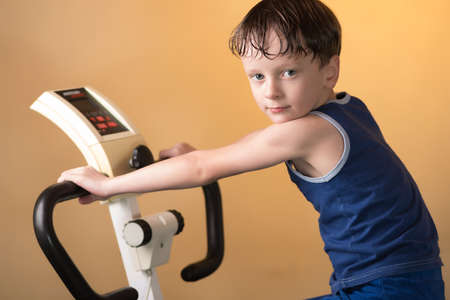 stationary bike: The child is trained on a stationary bike . Leads a healthy lifestyle. The boy develops muscles . Sport generation.