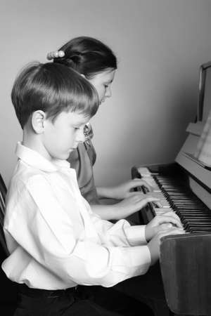 piano player: Boy and girl playing the piano at the same time together. Brother And Sister Playing Piano. Piano player. Stock Photo