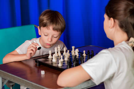 of boy and girl: Children spend a game of chess . Proceeds blitz chess tournament in the palace .