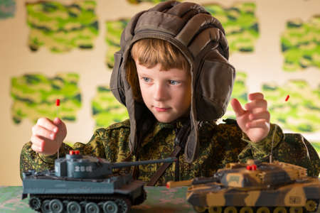 coloration: Boy playing toy. Radio-controlled toy military tank. Camouflage protective coloration .