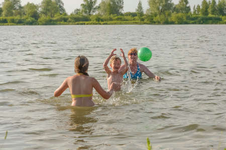 Family fun with a ball on the river in summer Stock Photo