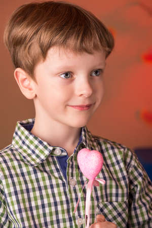 Boy holding a heart in his hands portrait Imagens