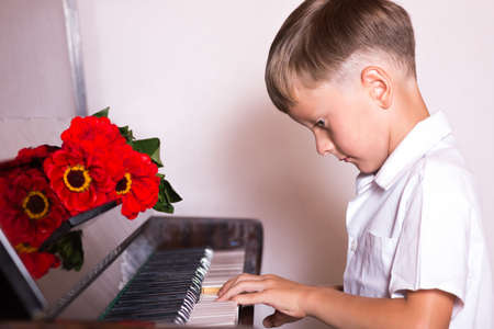 pianista: boy student pianist bestowed with a bouquet of red flowers from fans and viewers