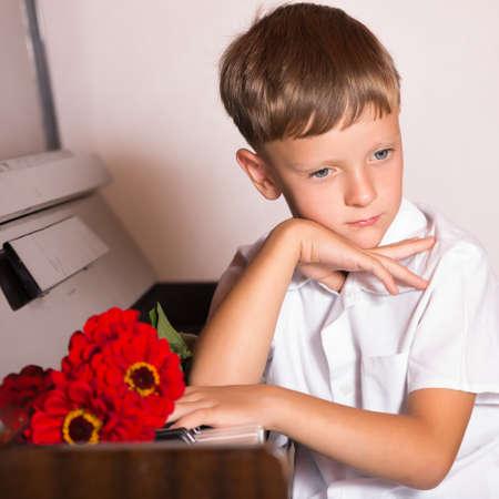 pianista: pianista niño estudiante otorgado con un ramo de flores rojas de los fans y espectadores