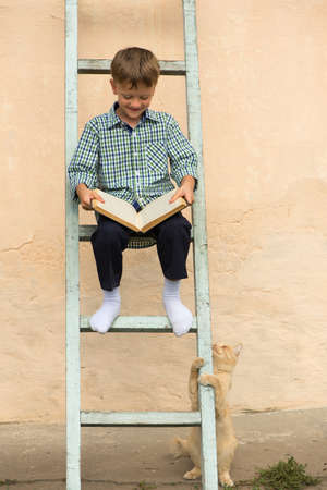 Boy sitting stairs. Read book. Human reading book ladder. Window and wall ladder.