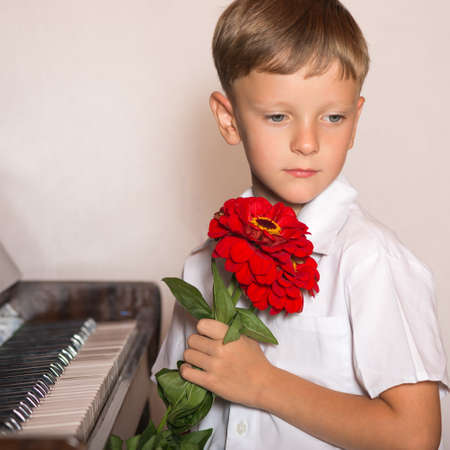 boy student pianist bestowed with a bouquet of red flowers from fans and viewers