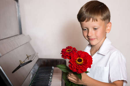 pianist: boy student pianist bestowed with a bouquet of red flowers from fans and viewers