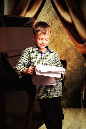 Boy with notes in their hands standing around the piano ready for action in front of the audience