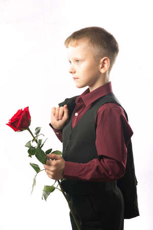 Portrait of a man with a red rose in his hand. Isolated on white background. Boy gives a flower. Guy bought flowers as a gift.