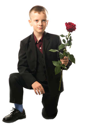 Young man is standing on one knee. Guy is holding a red rose in his hand. Isolated on white background. Boy gives a flower.