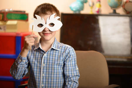 A young man with a mask for a masquerade. Different facial expressions and emotional moods. Stock Photo
