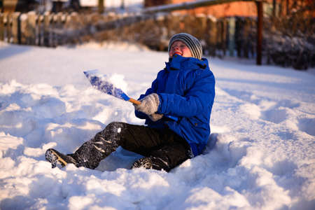 Guy in winter special clothes on a snow-covered field against the backdrop of a countryside landscape.Sits in the snow with a snowy childrens spatula in her hands. Stock Photo