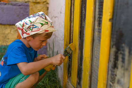 A boy performs a painting by dyeing the door in the open air summer outdoors. Restore order and improve appearance of the building.Stains the surface of the door squatting.