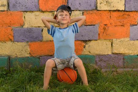 ボールを持った男は天然芝のカバーの上に座っている。難しく疲れた試合の後、私はバスケットボールのボールの上に座った。バスケットボールの