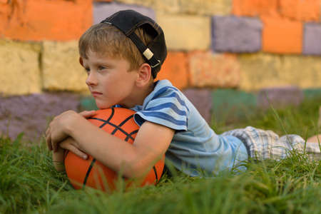 The guy with the ball lies on a natural grass cover. I put my head on the basketball. He pressed the ball with both hands. Playground for children for basketball.
