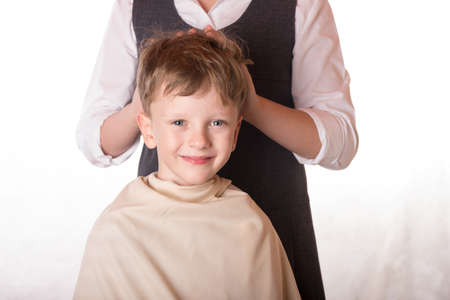 The hairdresser girl cuts the hair on the boys head. Makes hair styling. Hairdressing salon. Beauty saloon. The tousled hair laughs. Stock Photo
