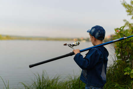 Attentive , focused, serious child is on a summer fishing on the river with a fishing rod in his hands.It stands on the river bank and tries to take away the spinning. Spin to the observers.