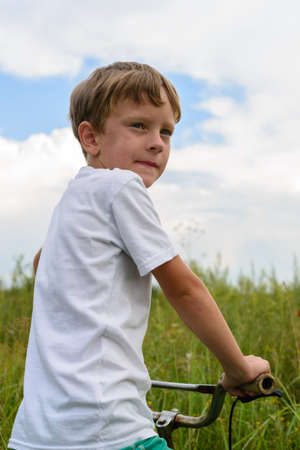 Boy riding a bike outdoors in the grass on a sunny day. A young man spends his free time on a pristine nature.He sits on the bicycles seat, turning sideways to those around him.