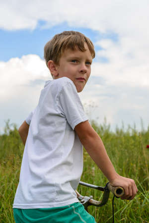 Boy riding a bike outdoors in the grass on a sunny day. A young man spends his free time on a pristine nature.He sits on the bicycle's seat, turning sideways to those around him.