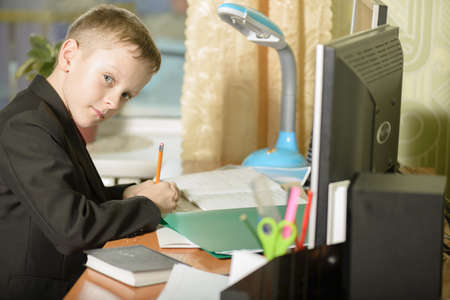 The guy at the office uses computer technology.The schoolboy writes with a pencil in a notebook at his desk. Stock Photo