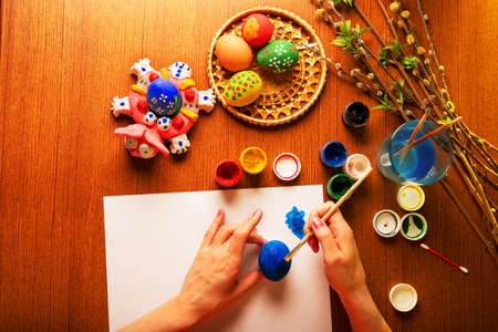 The artist paints Easter religious items. Chicken egg, prepared for coloring, is in the basket. Branches of willow and lilac with blooming green leaves. Paint in a jar with brushes and a glass of water. Hands close up.