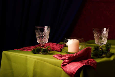 New Years still life. Glasses and a decanter from transparent glass. Festive feast. The table is laid by a black cloth. Xing pink background. The burning candle. Stock fotó