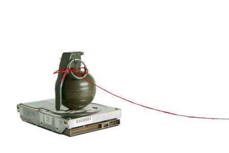 Hand grenade on top of a hard disk drive with red string attached to the pin. Good for demonstrating need for backups or possibly data volitility photo