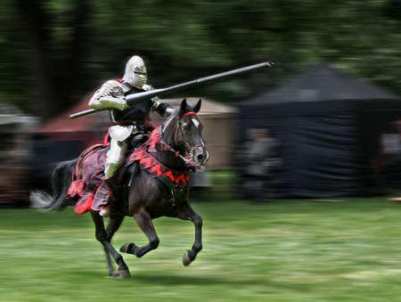 caballo jinete: Armored jinete con lanza a caballo. Motion fondo borroso.