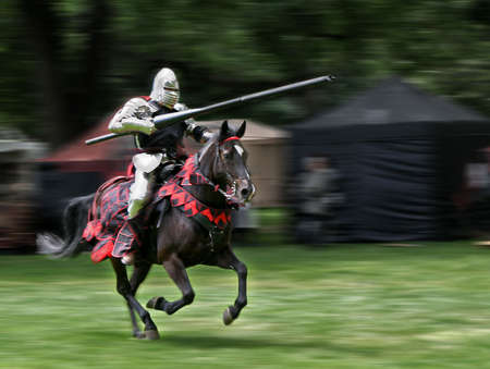 knight: Armored rider with lance on horse. Motion blurred background. Stock Photo