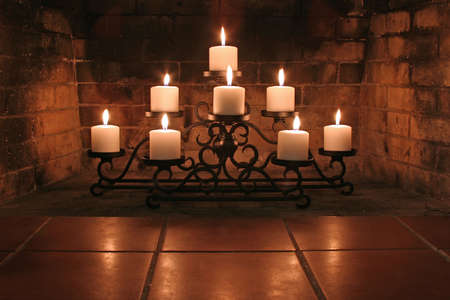 Fireplace candelabra with 8 candles projecting nice glow on bricks in background and reflecting in foreground.